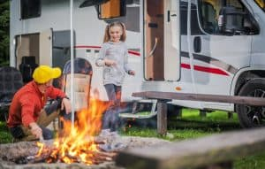 Family RV Road Trip Campsite. Caucasian Family. Father with Daughter Having Fun in Front of Campfire. Recreation Vehicle Traveling.