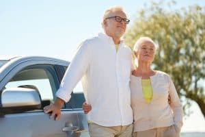road trip, travel and old people concept - happy senior couple hugging at car in summer